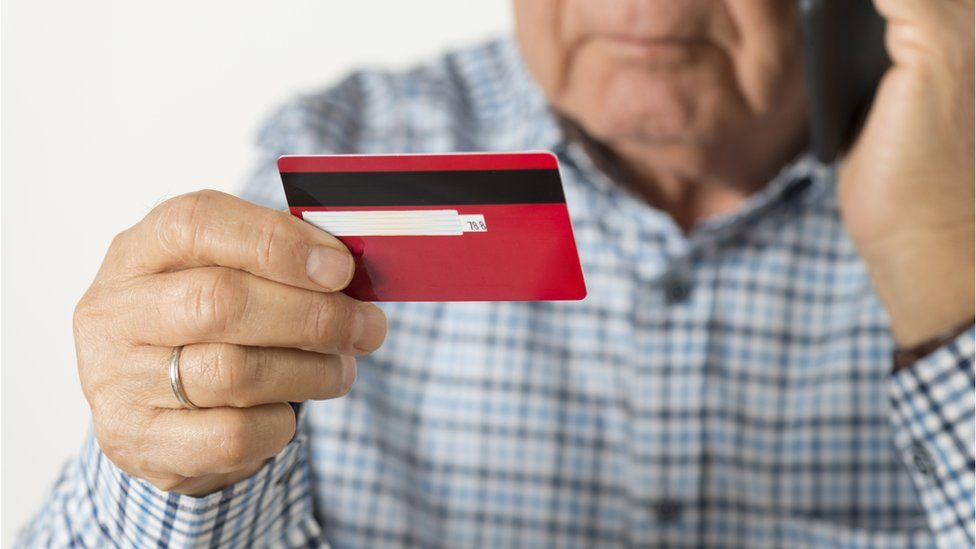 elderly man holding credit card while on the phone