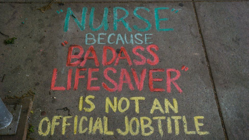 A note saying 'Nurse: Because Badass Lifesaver is not a Job Title' is left in chalk outside New York's Mount Sinai