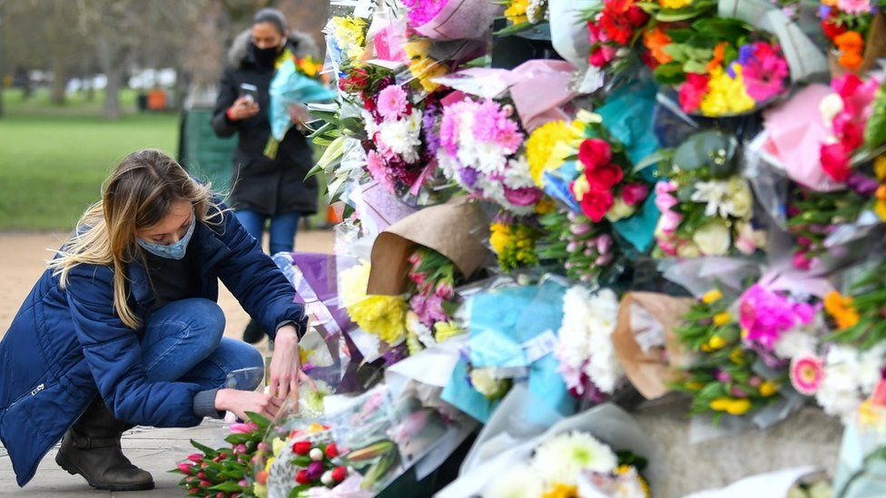 A woman lays flowers at the memorial site