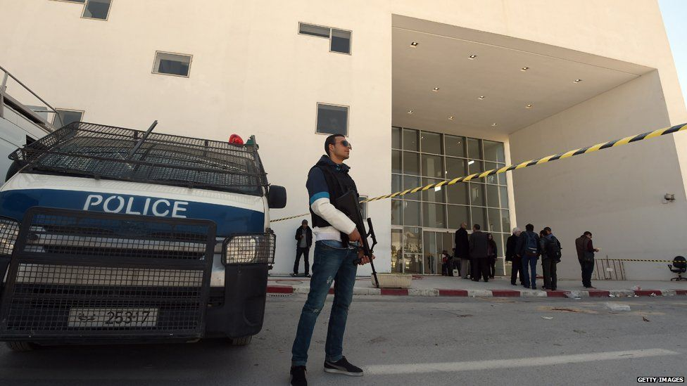 Tunisian security forces and forensic experts stand at the visitors entrance of the National Bardo Museum in Tunis on March 19, 2015, in the aftermath of an attack on foreign tourists.