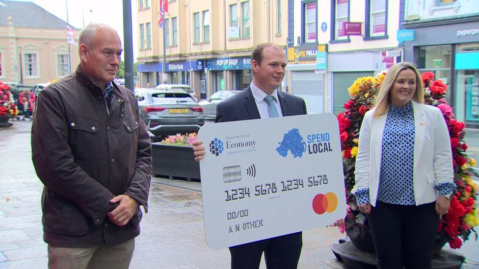 Gordon Lyons holds a giant version of the high street voucher on a street in Carrickfergus with two people next to him