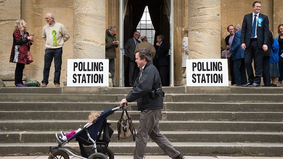 Members of the public arrive to cast their votes at a polling station in Chipping Norton town hall