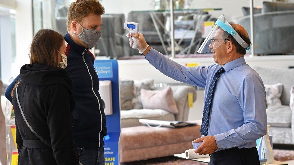 """A member of staff wearing a face shield uses a laser thermometer to test a customer""""s temperature in a Furniture Village store in Croydon, in south-east London on June 5, 2020, following the easing of the lockdown restrictions during the novel coronavirus COVID-19 pandemic."""