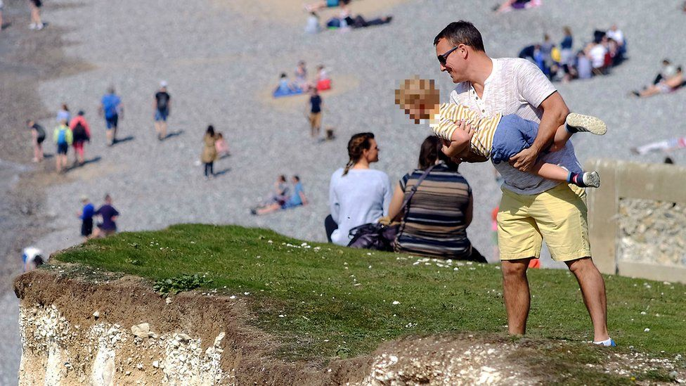 A man was spotted lifting a child o peer over the cliff edge at Seven Sisters