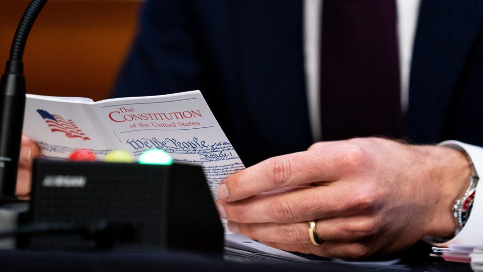 US Sen. Josh Hawley (R-MO) holds a small U.S. Constitution book while Supreme Court nominee Judge Amy Coney Barrett testifies before the Senate Judiciary Committee on Capitol Hill on 13 October 2020 in Washington, DC