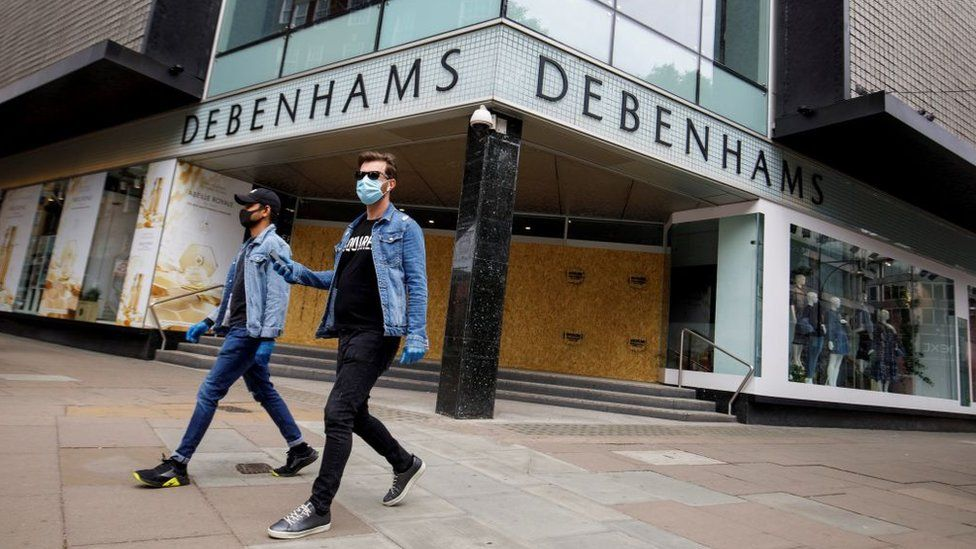 Two people wearing masks walk past a boarded-up Debenhams store in Oxford Street, London