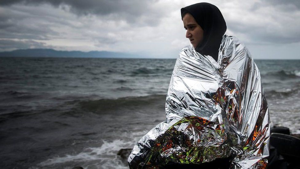 A woman tries to warm up herself using a thermal blanket provided by volunteers after arriving on a dinghy from a Turkish coast to the north-eastern Greek island of Lesbos, Saturday, Oct. 24, 2015