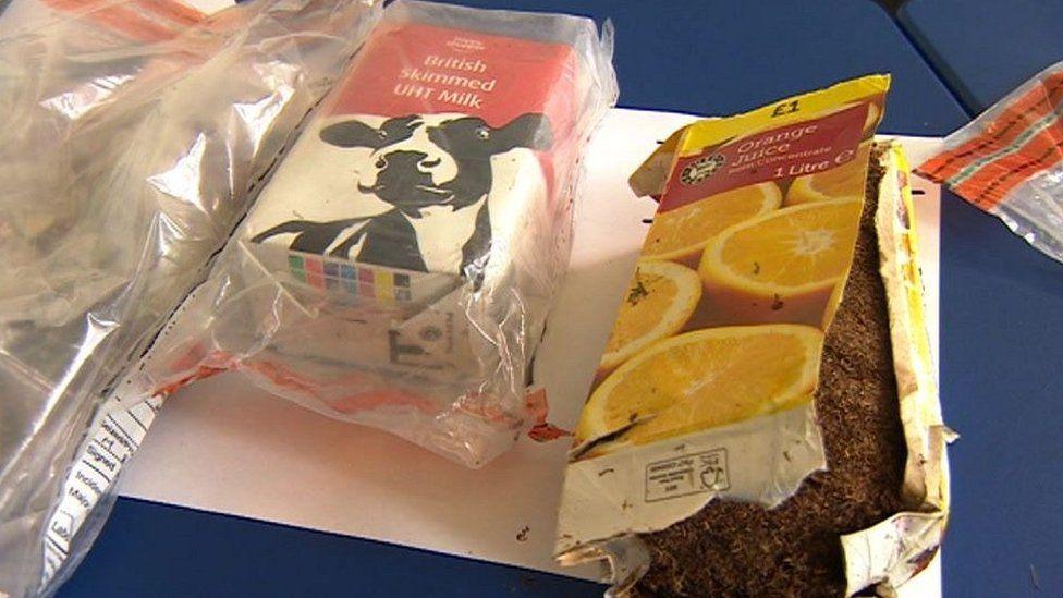 Carton of orange juice and a milk carton with smuggled contraband items hidden inside