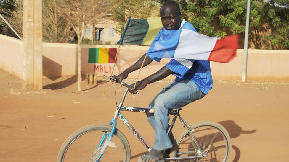 A man in Mali with Malian and French flags flying from his bicycle