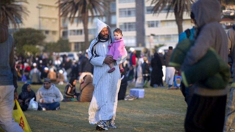 A man walks with a child as Muslim people congregate at Seapoint Promenade, a popular public area next to the sea, to try to sight the new moon, which will signify the end of the Muslim holy month of fasting, called Ramadan, on July 27, 2014.