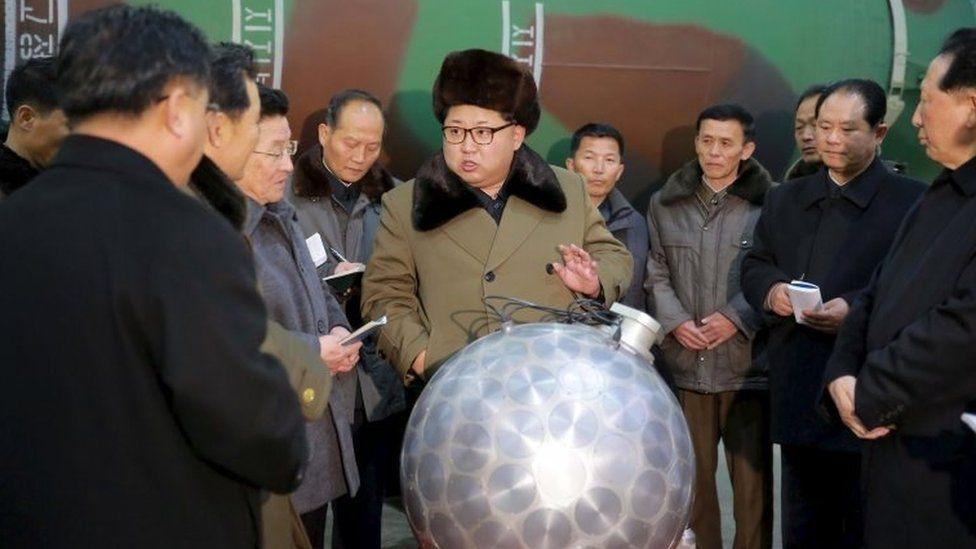 North Korean leader Kim Jong-un speaks to scientists next to what the North claims is a model of a miniaturised hydrogen bomb (9 March 2016)