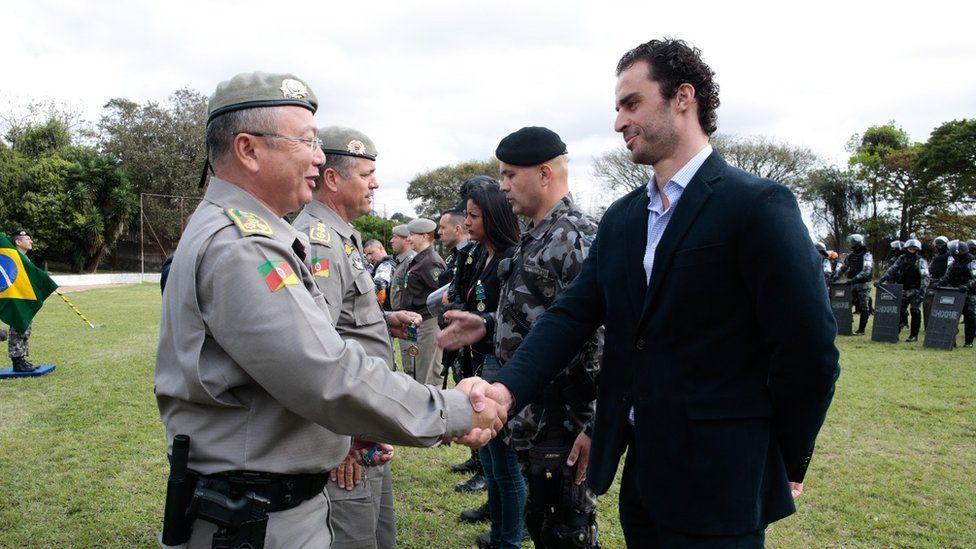 Leo Fração shakes the hand of a member of the military police