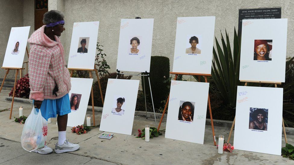A woman views photographs set up as a memorial for 10 of the victims of the serial killer dubbed the 'Grim Sleeper'