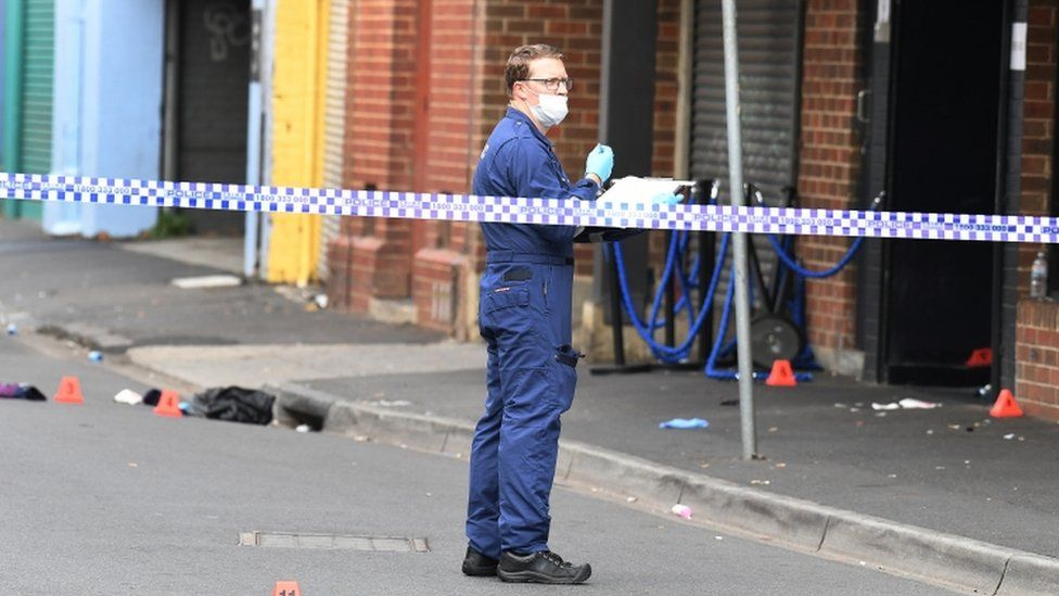 A forensic police officer is seen behind police line tape