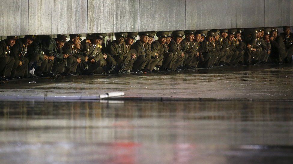Soldiers sheltering from the rain after the military parade for the 70th anniversary of the founding Workers' Party, Pyongyang, North Korea - Saturday 10 October 2015