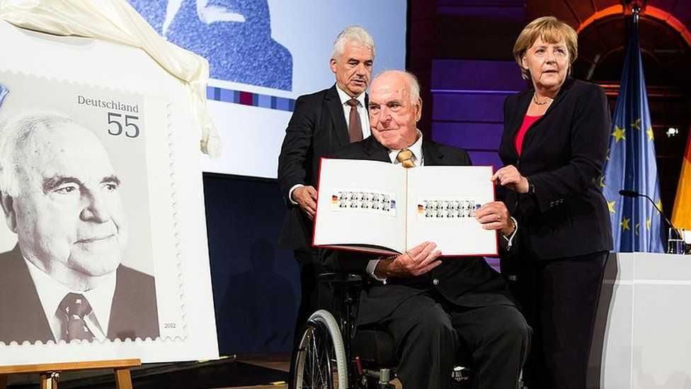 A 2012 picture of Angela Merkel presenting a commemorative postal stamp showing former German Chancellor Helmut Kohl as he looks on