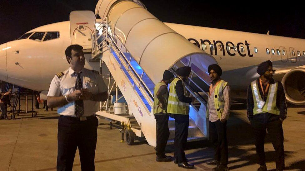 Ground staff stand near a Jet Airways Jet Konnect jet ahead of a flight from Amritsar to Mumbai, then Delhi. The flight was Jet Airways last before suspending all flights