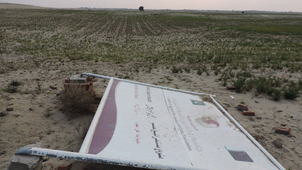 A collapsed signboard of the Jassim & Hamad bin Jassim Charitable Foundation of Qatar shows a tract of land donated by locals for a hospital near Hyderabad Thal town.