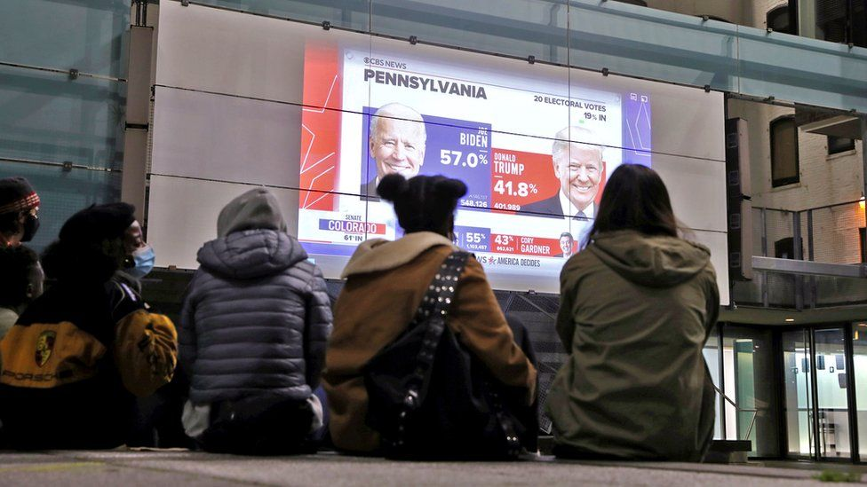 People watch early results on a large outdoor screen