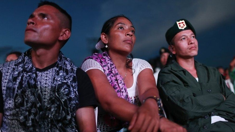 Revolutionary Armed Forces of Colombia (FARC) rebels watch a live broadcast of the peace agreement ceremony while at a FARC encampment in the remote Yari plains where the peace accord was ratified by the FARC on September 26, 2016 in El Diamante, Colombia.