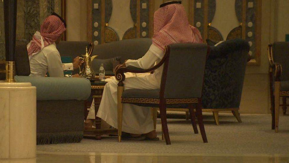 Saudi men in traditional dress sit in chairs in the Ritz Carlton in Riyadh, drinking coffee.