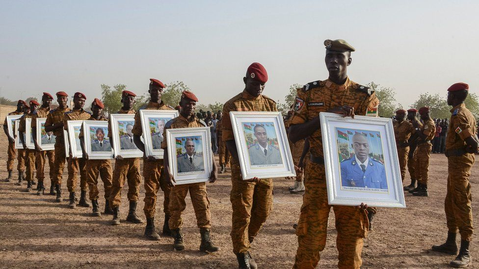 Soldiers of the Burkina Faso's Armed Forces on 20 December carry the portraits of 12 servicemen killed during a Jihadist attack a few days earlier.