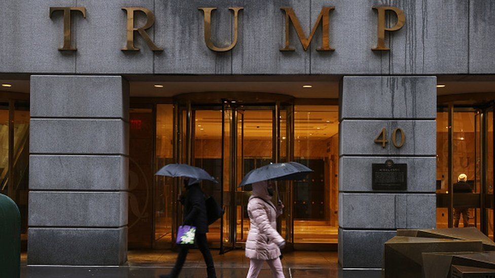 People walk by a Trump-owned property on Wall Street
