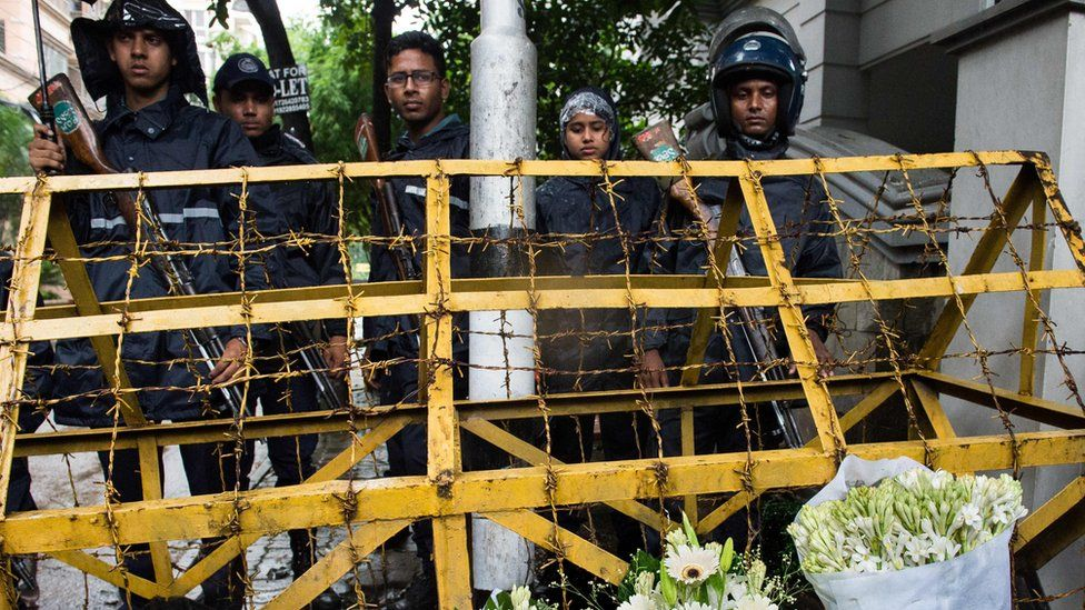 Bangladeshi policemen guard a check point where floral arrangements have been left by well-wishers on a road leading to an upscale cafe that was the site of a bloody siege in Dhaka, 3 July 2016
