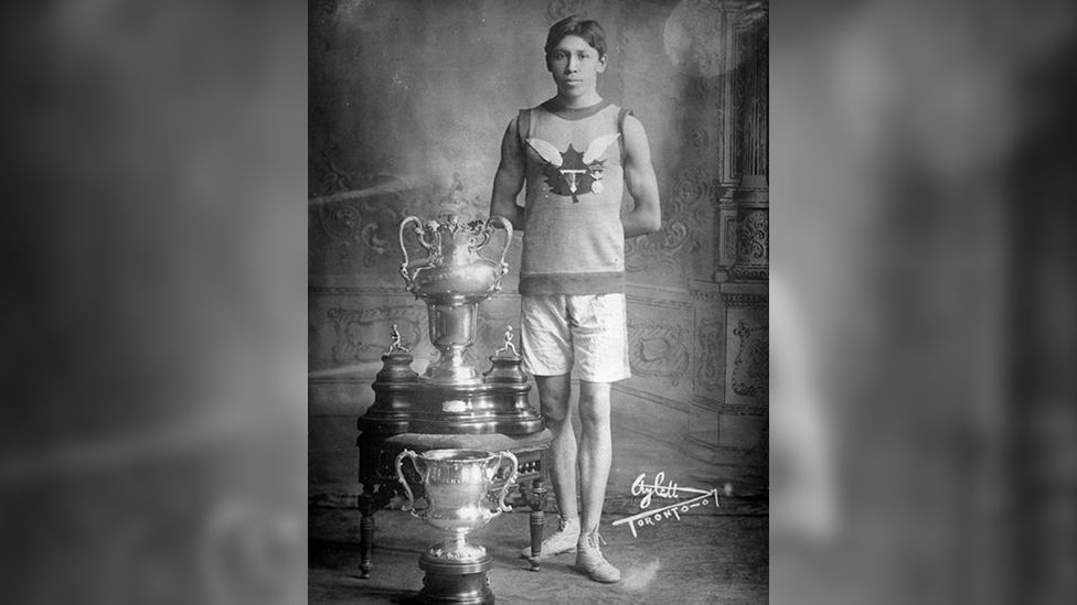 Tom Longboat posing with running trophies