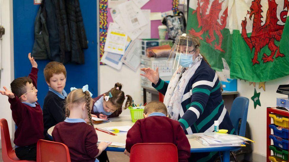 A teacher wearing a face mask and visor while teaching pupils