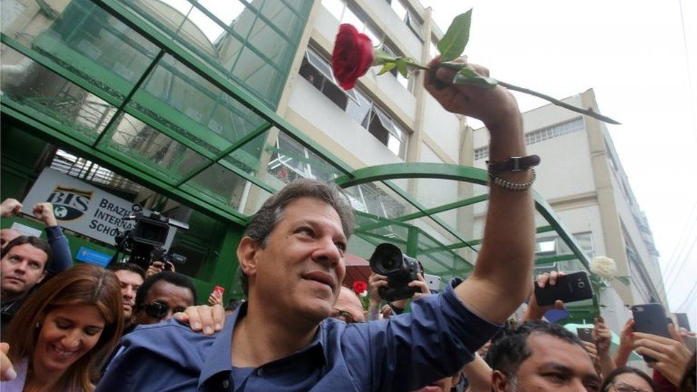Fernando Haddad waves a red rose after casting his vote