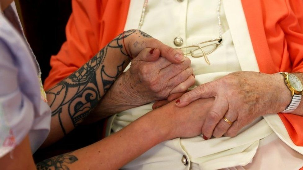 Care home worker holds resident's hand