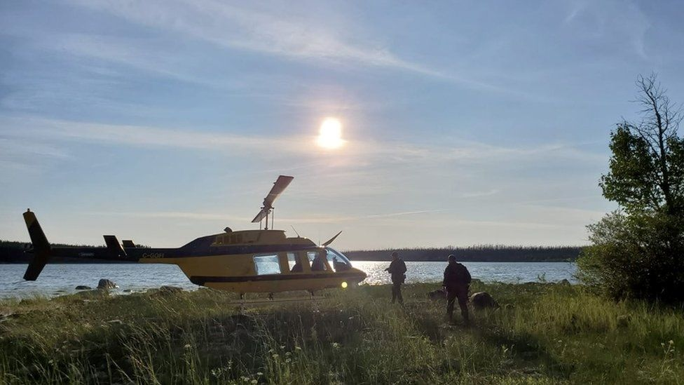 Police approach a search helicopter in the Manitoba wilderness.