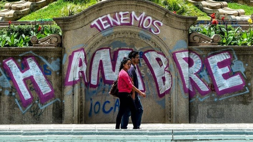 """A couple walks by graffiti reading """"We Are Hungry"""" in Caracas on August 8, 2017."""