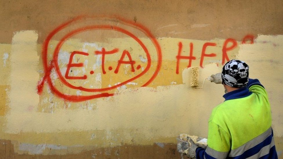 """A municipal worker paints over graffiti reading """"ETA, The People Are With You"""" the day after Basque separatist group ETA announced a definitive cessation of armed activity, in the Basque town of Guernica, Spain (21 October 2011)"""