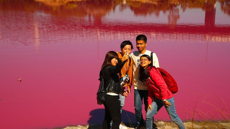 A group of tourists take a selfie in front of the pink lake at Westgate Park