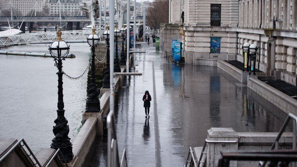A woman walks along South Bank in London