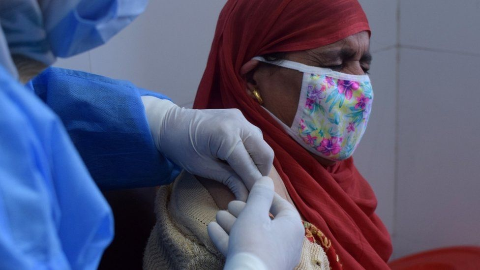 A woman reacts as she receives a dose of COVISHIELD, a coronavirus disease (COVID-19) vaccine manufactured by Serum Institute of India, at a vaccination centre in Srinagar.