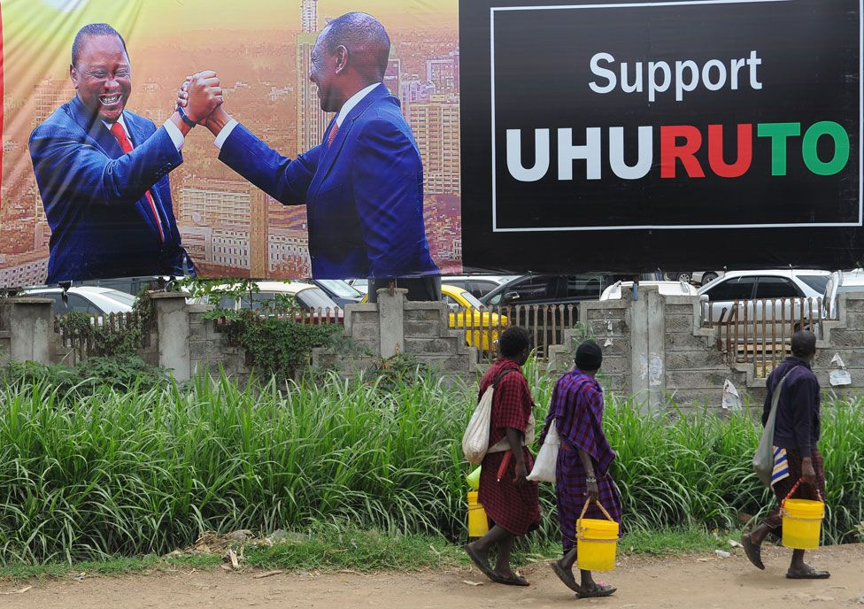 Pedestrians walk past the campaign poster of Kenya's President Uhuru Kenyatta and Deputy-President William Ruto in Nairobi on October 23, 2017, ahead of the repeat elections. Kenyans head to the polls on October 26 for a second time this year after the Supreme Court overturned the August election victory of President Uhuru Kenyatta.
