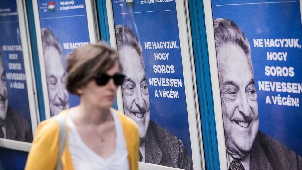 A woman walks past a wall of Soros posters
