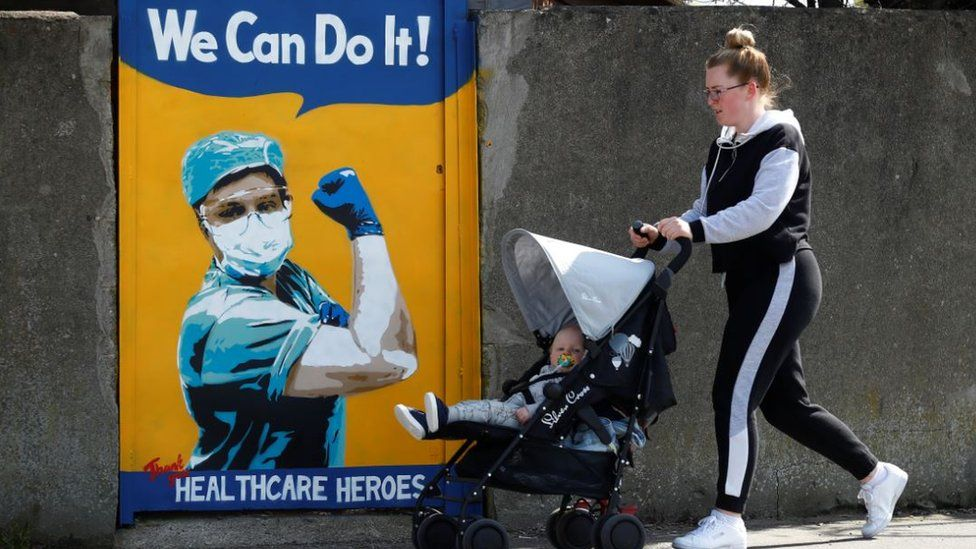 A woman pushes a child in a buggy past an NHS mural by Emma Blake in Dublin