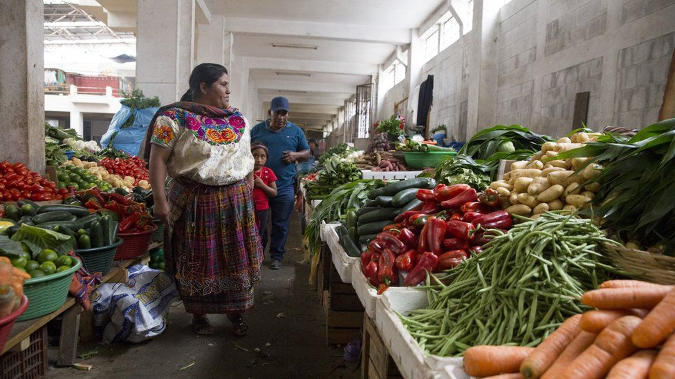 A family shops for vegetables at a market in Zunil