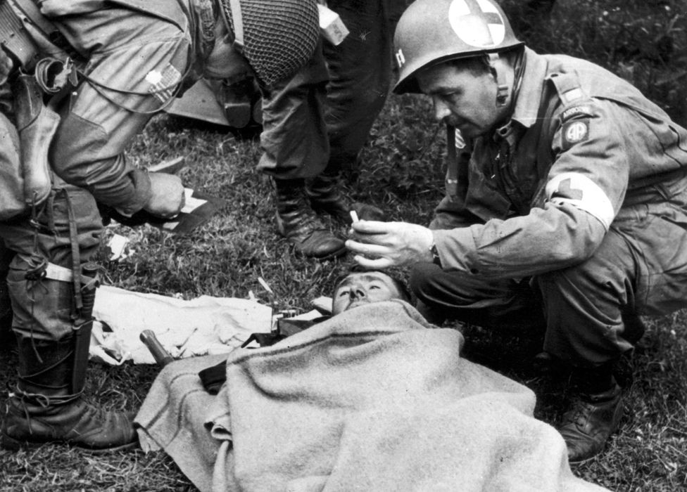 A doctor of the US 82nd Airborne division cares for a wounded German prisoner in Normandy