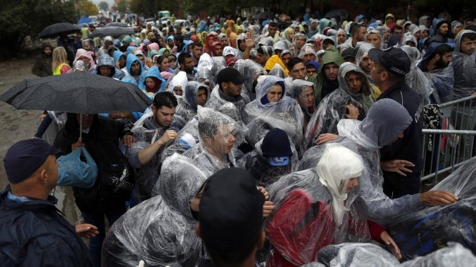 Police try to control the crowd as migrants enter to registration centre in the southern Serbian town of Presevo, 7 Oct 2015