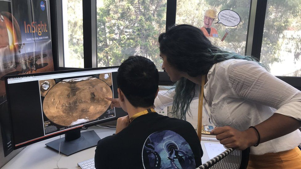 Two people look at a screen with a map of Mars - we are looking over their shoulders