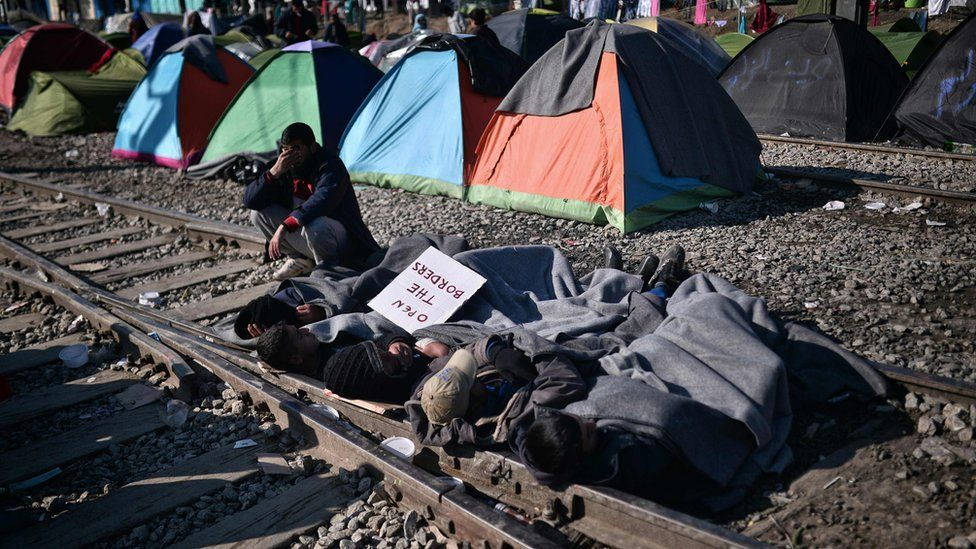 "Men lay on railway tracks as a form of protest as they hold a banner reading ""Open the border"" at a makeshift camp by the Greek-Macedonian border near the village of Idomeni, 20 March 2016"