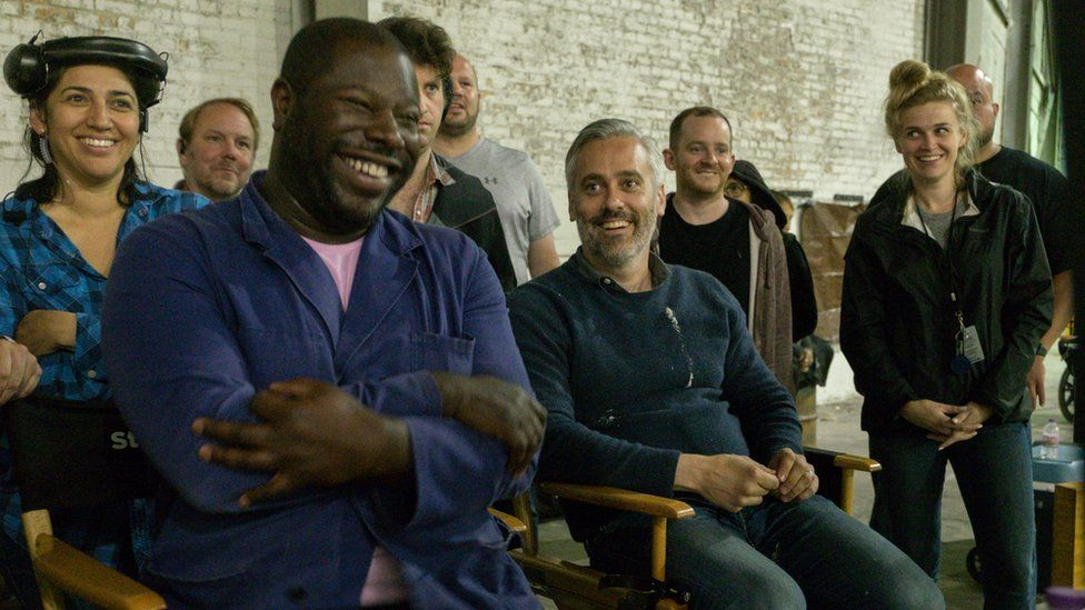 Steve McQueen on set with producer Iain Canning and other crew members