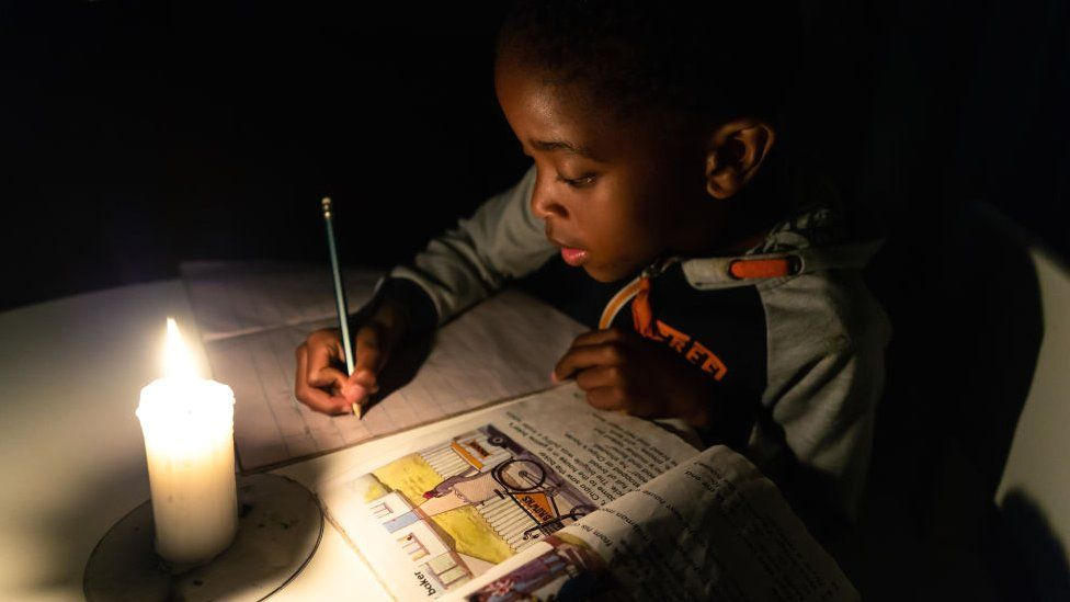 A child doing his homework by candlelight in Harare, Zimbabwe - June 2019