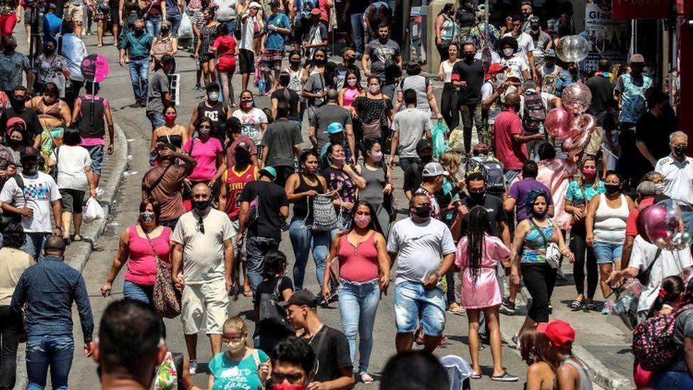 Dozens of people walk along a shopping street in downtown São Paulo, Brazil, 7 October 2020.