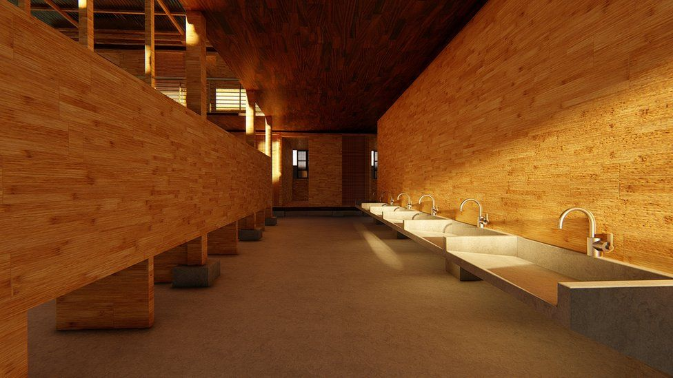 A row of sinks inside the house bathed in a golden glow as sunshine hits the bamboo walls